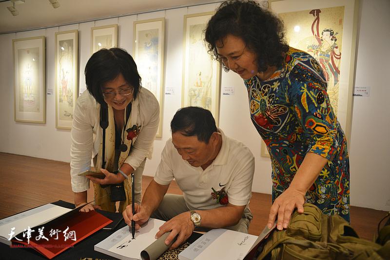刘志君在朵云轩美术馆为观众签名留念。