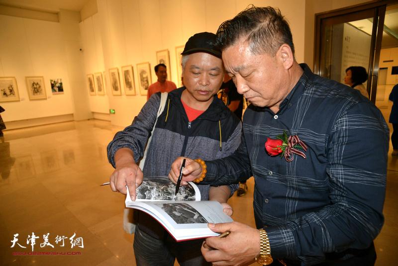 皮志刚在朵云轩美术馆为观众签名留念。