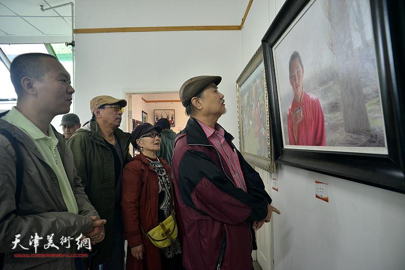 张树德、吴薇、郑爱民、何成欣赏展出的画作。