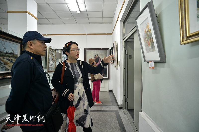 杨健、刁孟榕欣赏展出的画作。