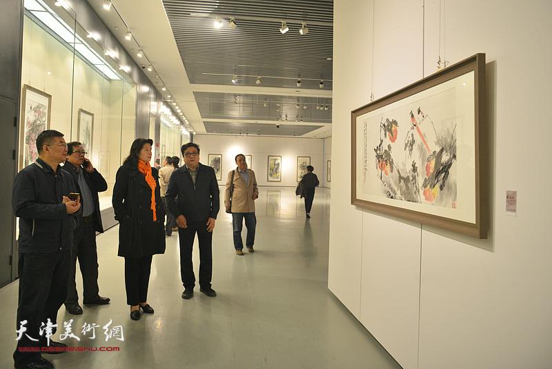 万镜明、商移山、冉繁英、李延春在画展现场观看作品。