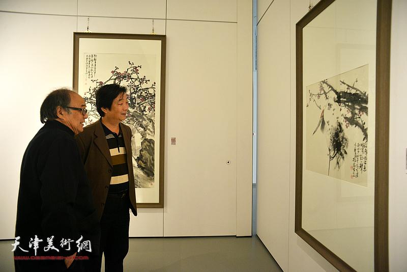 郭书仁、翟洪涛在画展现场观看作品。