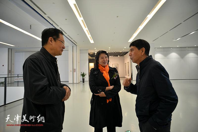 万镜明、张寿庠、潘津生在画展现场交流。