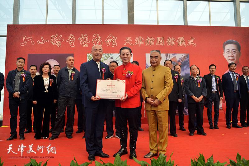 章金莱、林德谦向杜彦峰颁发收藏证书。