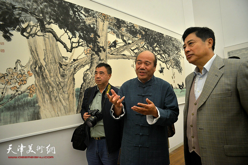 孟庆占陪同董伟观赏展出的作品。