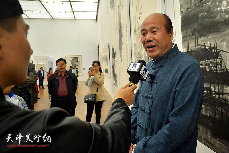 文化部中国艺术研究院特聘研究员、天津美术家协会副主席孟庆占在现场接受媒体采访。