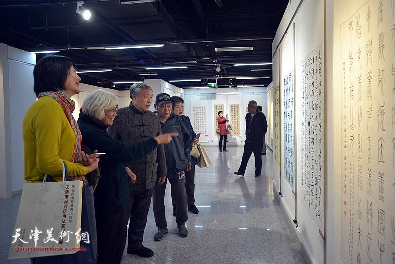 唐云来、刘春雨在展览现场与参展作者、观众观赏作品。
