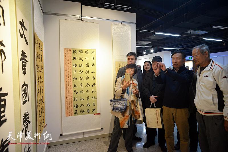 张建会在展览现场与参展作者、观众观赏作品。