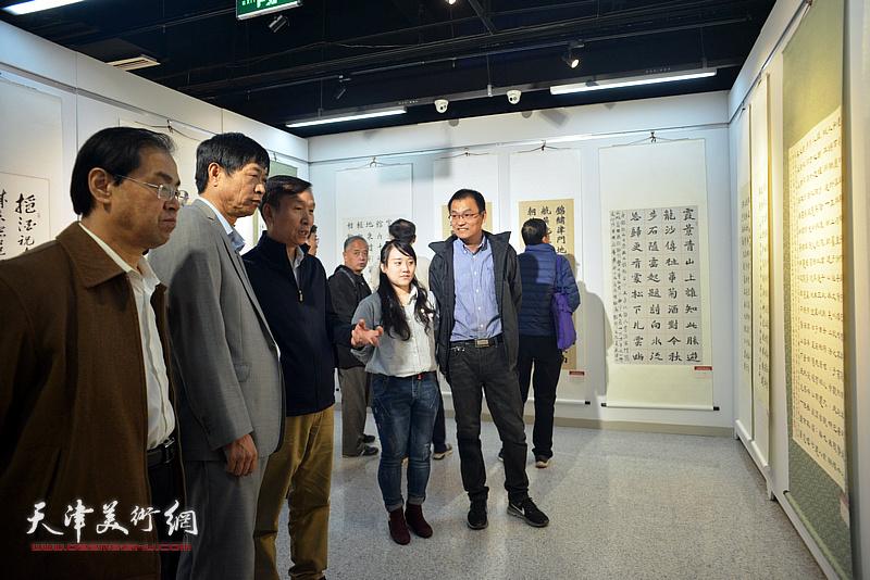 张建会在展览现场为参展作者点评展品。