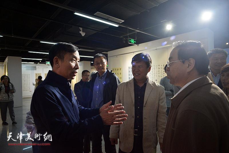 张建会、田树仁、赵宝琴在展览现场交流。
