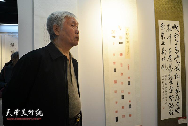 袁健民在展览现场观赏展品。