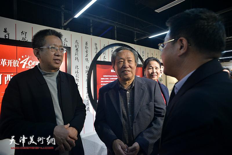 李毅峰、刘国胜、怀远在画展现场交流。