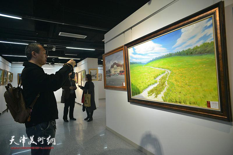 何成在画展现场拍下展出的画家张志德的油画作品。