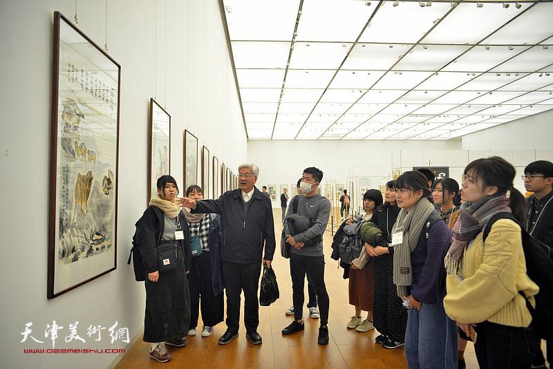 曹柏崑在展览现场为青年画家讲解作品。