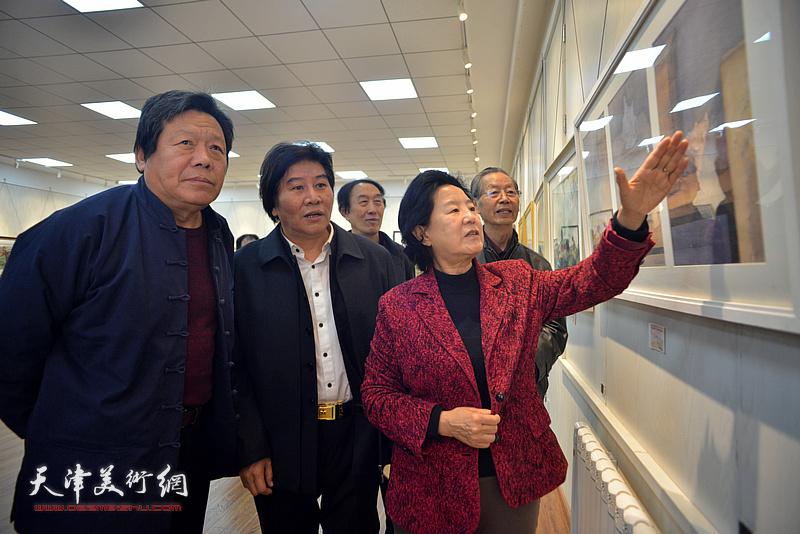 曹秀荣、刘建华、郭鸿春、李岳林、高学年在画展现场观看作品。