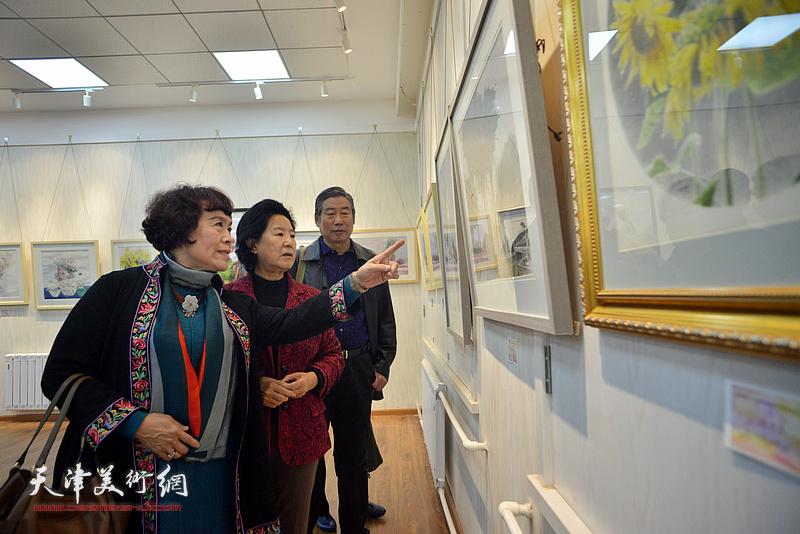 曹秀荣、史玉、胡万荣在画展现场观看作品。