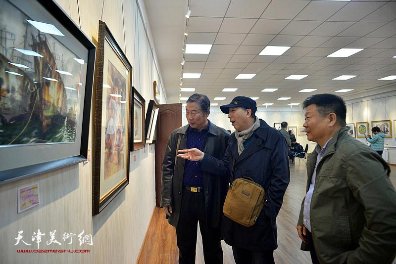 帅起、胡万荣、陶国柱在画展现场观看作品。