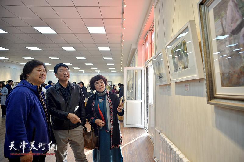 刘文生、姜中立、史玉在画展现场观看作品。