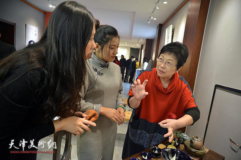 林映汝向刘彦均、西贝介绍她制作的陶艺。