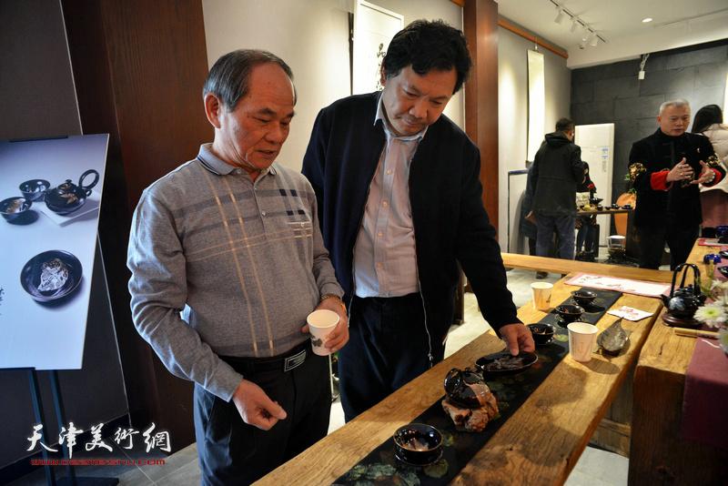 秀夫、黄瑞兴在现场欣赏林映汝的陶艺作品。