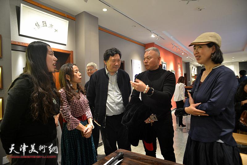张俊国、秀夫、郑淋在陶艺作品展现场交流。