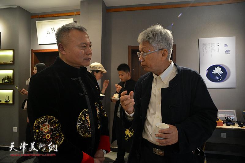 张俊国与来宾在陶艺作品展现场交流。