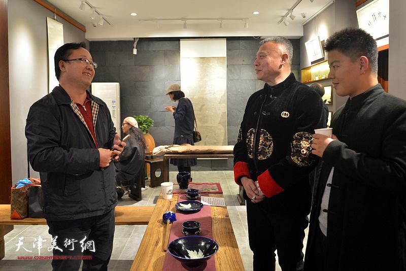 张俊国、孙志远在陶艺作品展现场交流。