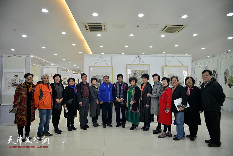 参展画家何荣洪、高学年、史玉与来宾在画展现场。