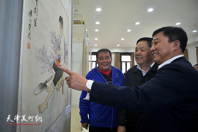 史毓春、刘光欣、何荣洪在画展现场观赏展出的作品。