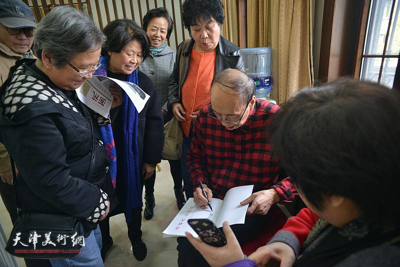 张学强在画展现场为观众签名留念。