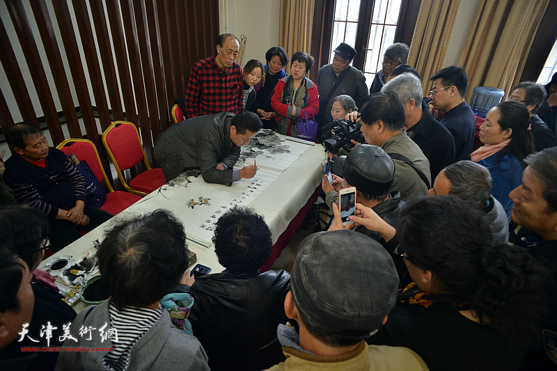张学强、王鸿鑫在画展现场创作。