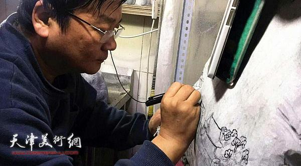 杜雷在创作大型翡翠玉雕《赶大营风云录》。