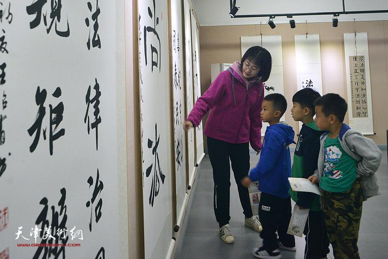 老师在展览现场为小观众们讲解作品。