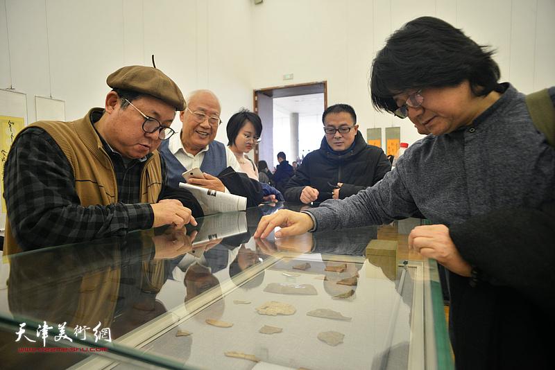酆耀国、张同明、赵清、乔瑞民在展览现场观看展出的甲骨文实物。