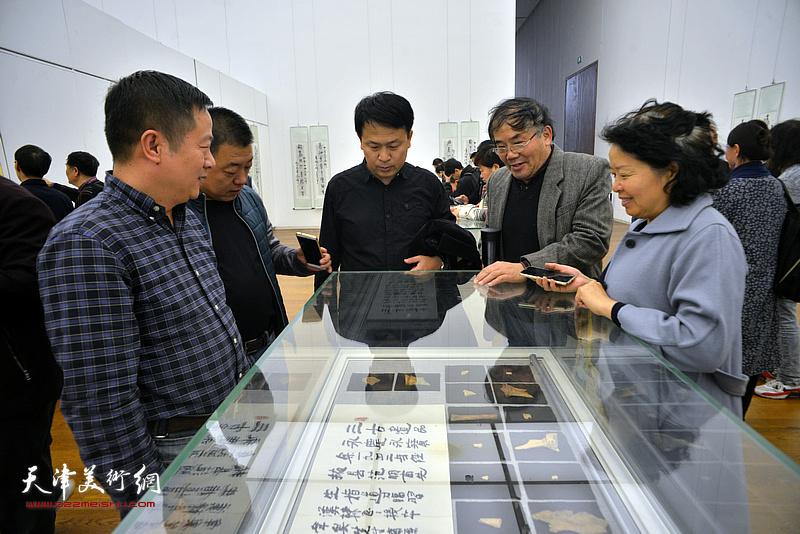 张洪春、唐镁、沈蕴杰在展览现场观看展出的甲骨文实物。