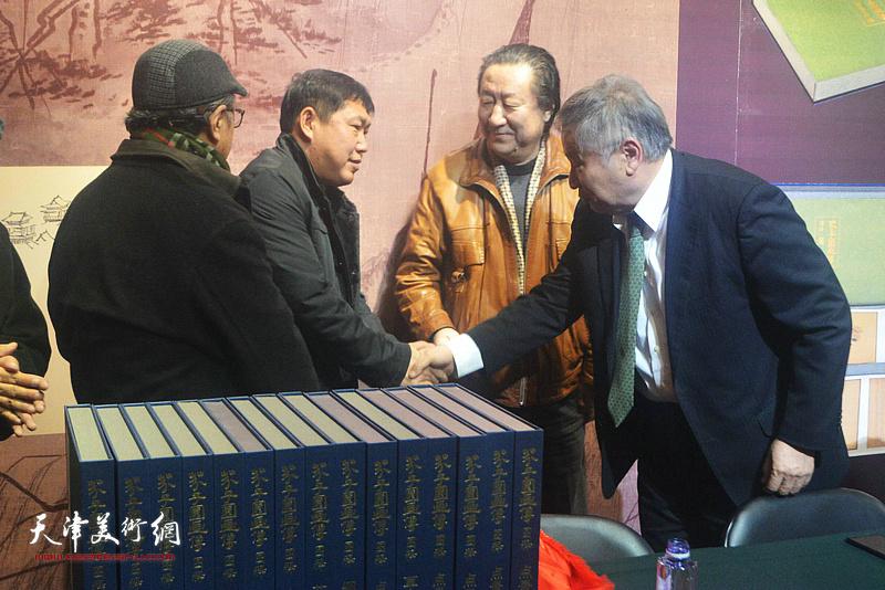 杨晓阳、李庚、李宝林向高振祝贺《芥子园画传图释》出版成功。