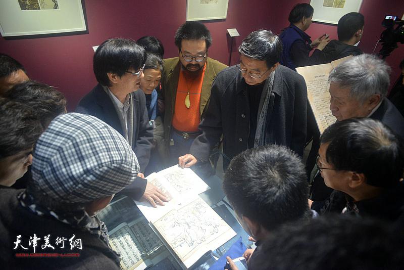 李庚、王鲁湘、陆宗渊观赏《芥子园画传》的古版本。