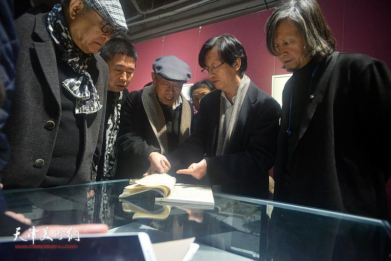 薛永年、姜宝林、陆宗渊观赏《芥子园画传》的古版本。