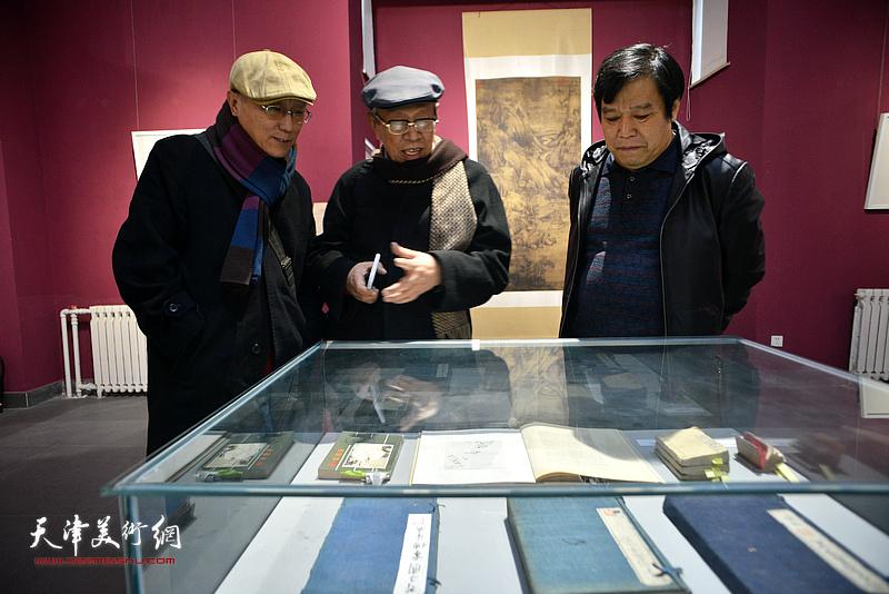 薛永年、李耀春、何东观赏《芥子园画传》的古版本。