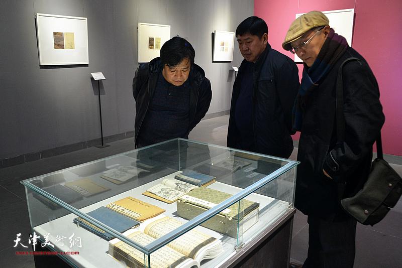 高振、李耀春、何东观赏《芥子园画传》不同时期的版本。