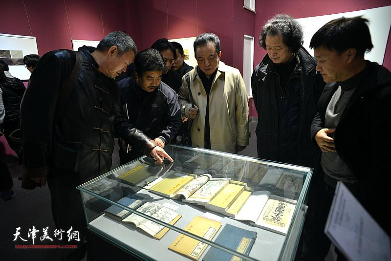 桂晓风、奚天鹰、吴涤生观赏《芥子园画传》不同时期的版本。
