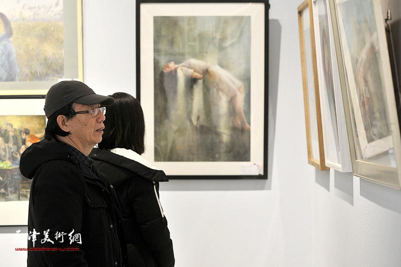 庞恩昌在观赏展出的画作。