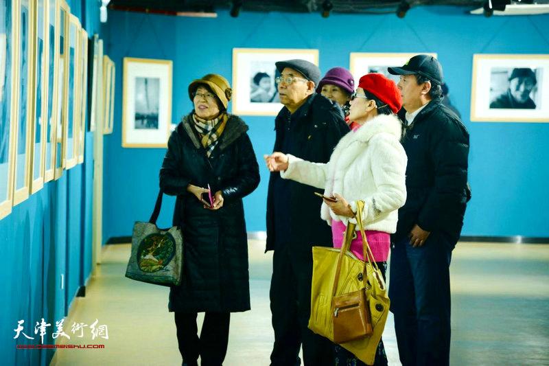 图为美术、摄影爱好者在展览现场观赏展品。
