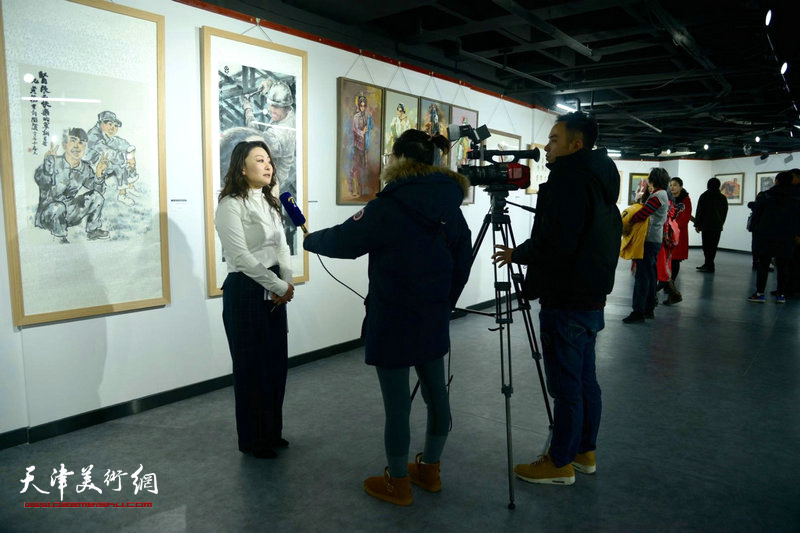 图为邢晓阳在展览现场接受媒体采访。