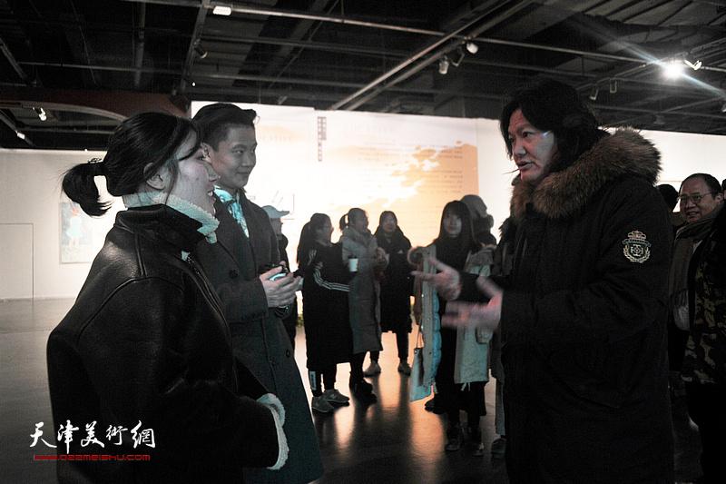 曹敬钢与青年艺术家在画展现场交流。