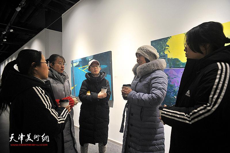 王红与青年艺术家在画展现场交流。