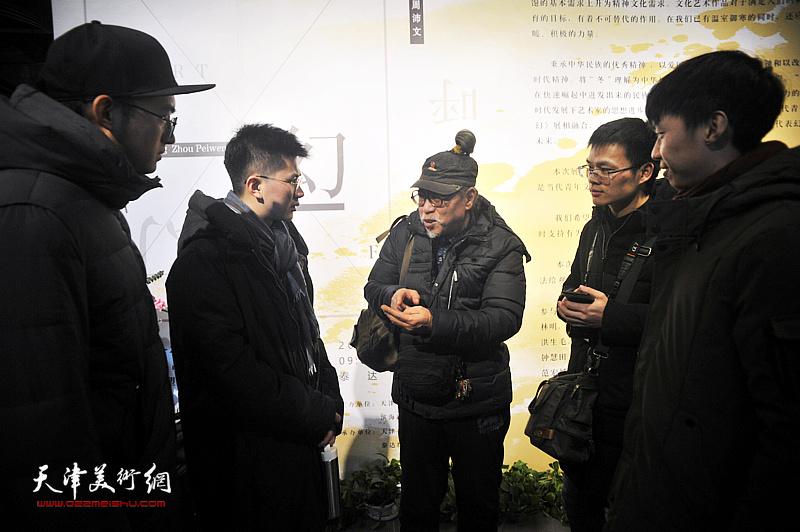 赵潭与青年艺术家在画展现场交流。