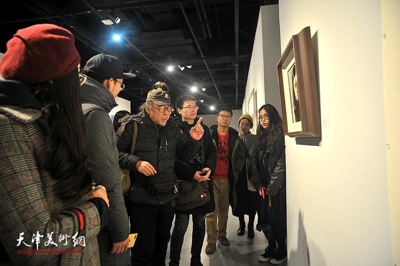 赵潭与青年艺术家在画展现场分析作品。