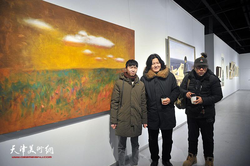 青年艺术家刘艳荣与曹敬钢、赵潭在展出的作品《风景》前。