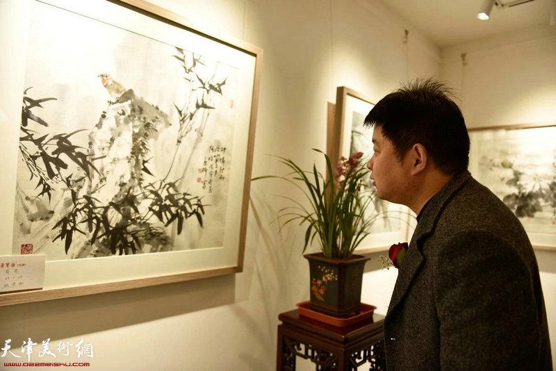 郭智文先生在观赏展出的作品。